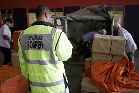 Diplomatic security courier supervising workers for Consul container
