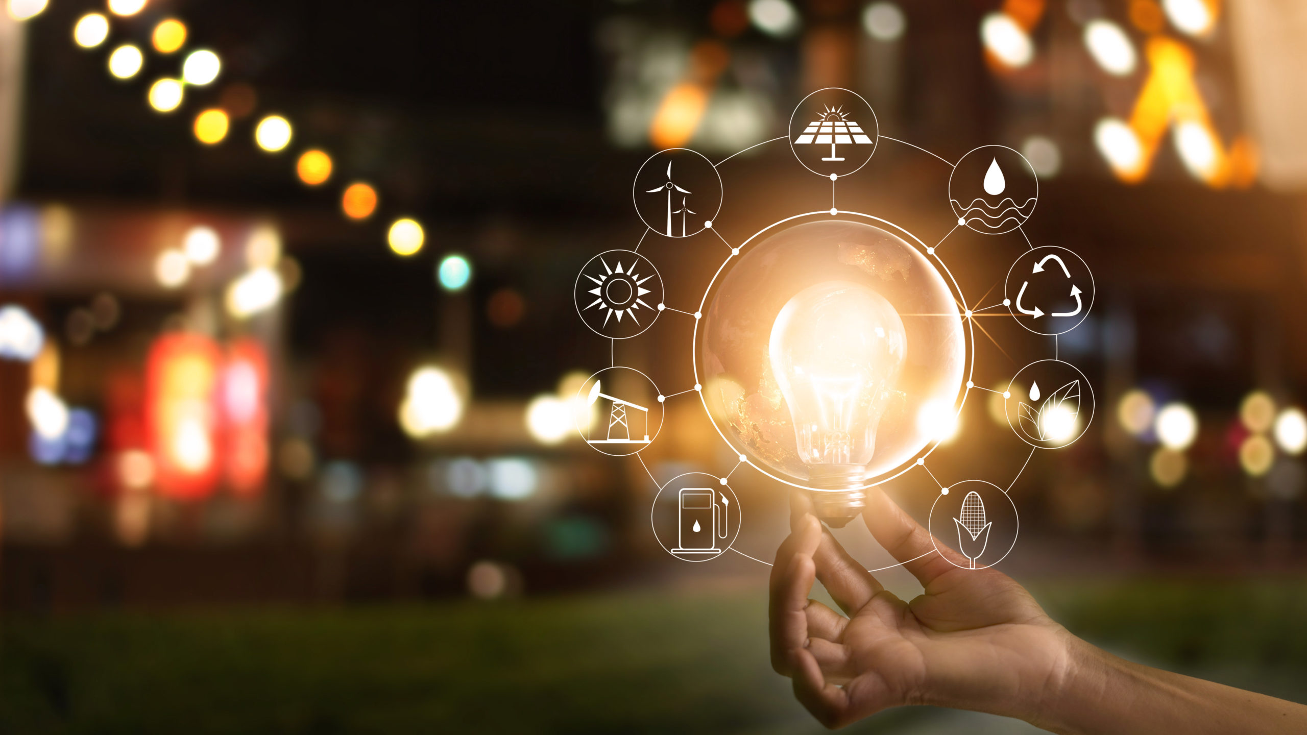 Hand holding light bulb in front of global show the world's consumption with icons energy sources for renewable, sustainable development. Ecology concept. Elements of this image furnished by NASA. - Image
