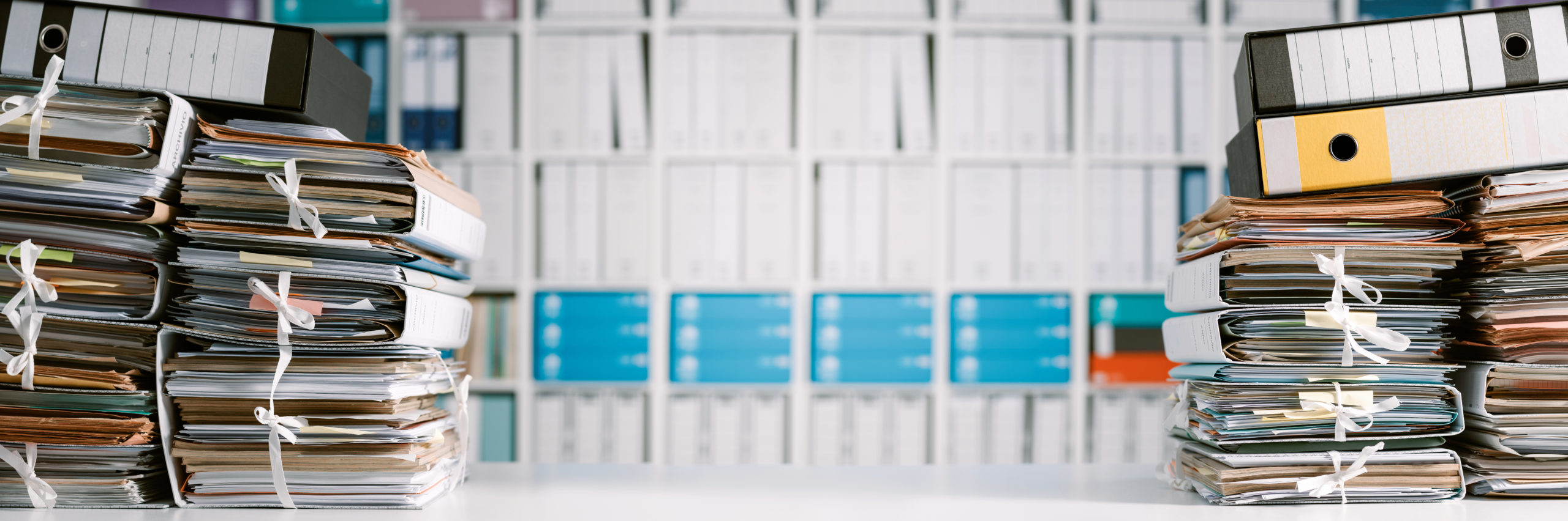 Stacks of files and paperwork in the office and bookshelves on the background: management and archive concept - Image