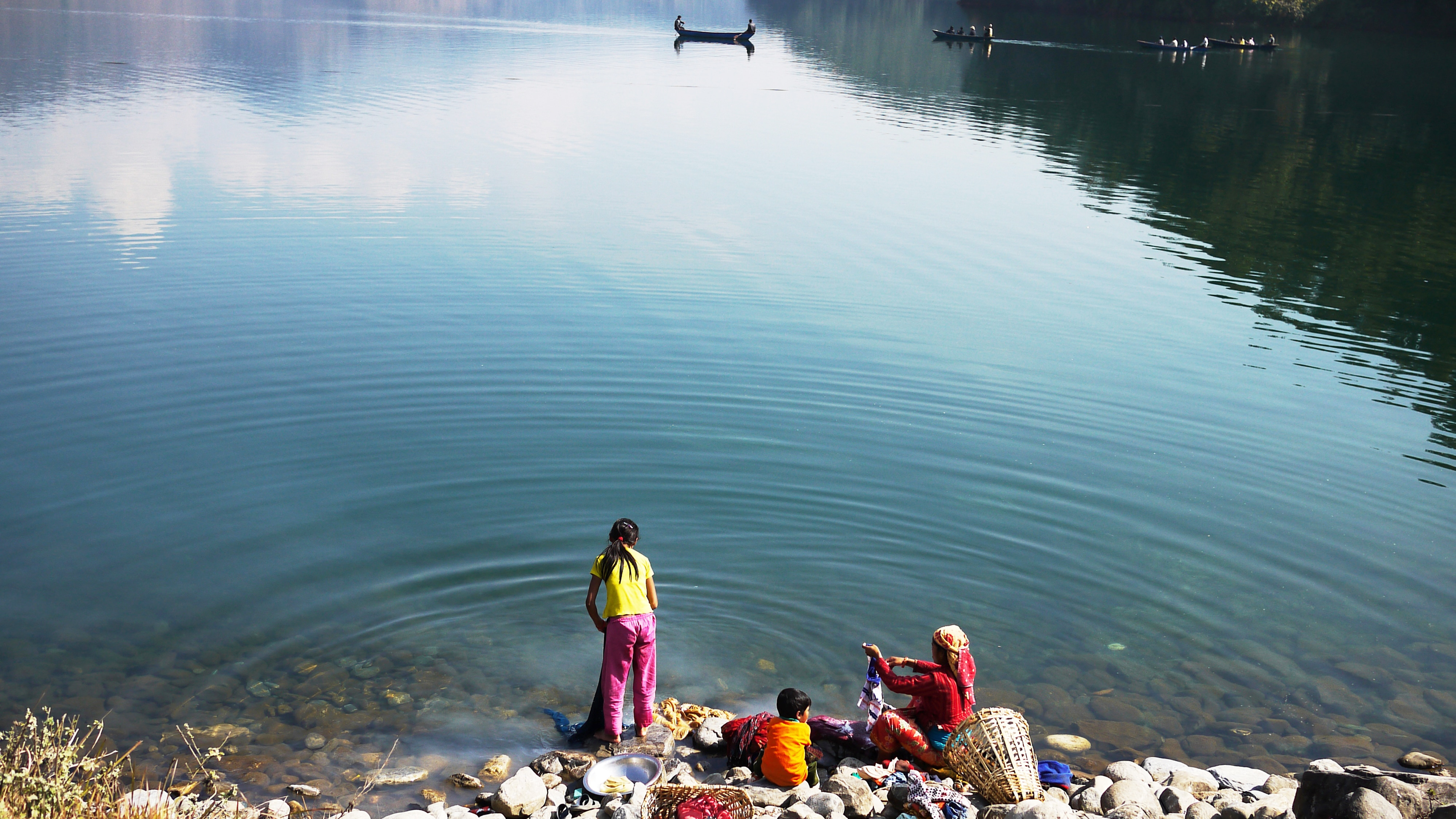 Family washing cloth in the Pokhara lake of reflection of sky and clouds in countryside pokhara, nepal, southern asia developing country, Simply life - Image