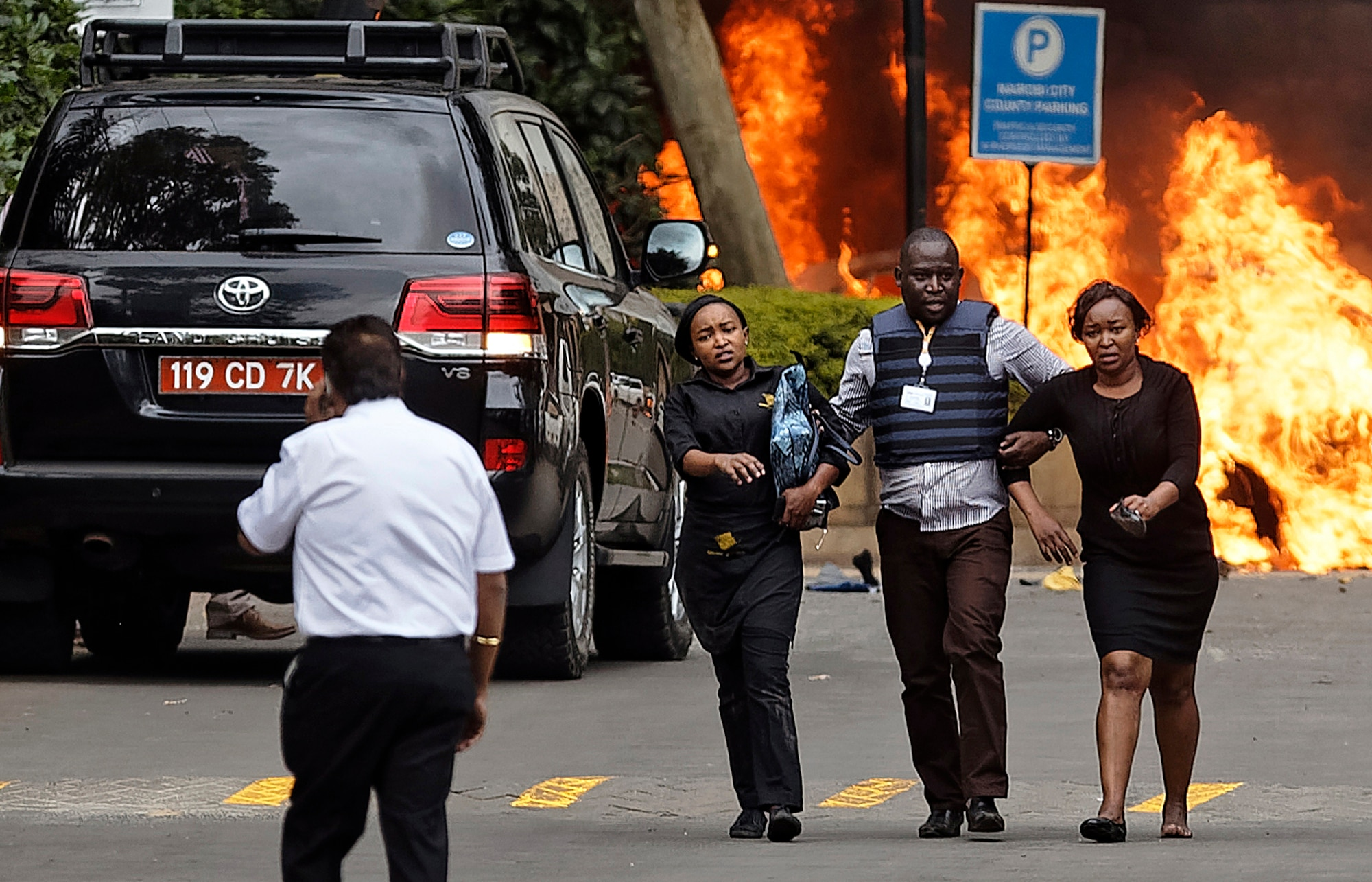 Security forces help civilians flee the scene as cars burn behind, at a hotel complex in Nairobi, Kenya Tuesday, Jan. 15, 2019. Terrorists attacked an upscale hotel complex in Kenya's capital Tuesday, sending people fleeing in panic as explosions and heavy gunfire reverberated through the neighborhood. (AP Photo/Ben Curtis) A private security officer helps civilians flee gunmen and burning cars during a terrorist attack at the DusitD2 Hotel complex in Nairobi, January 15, 2019. (AP/WideWorld Photos)