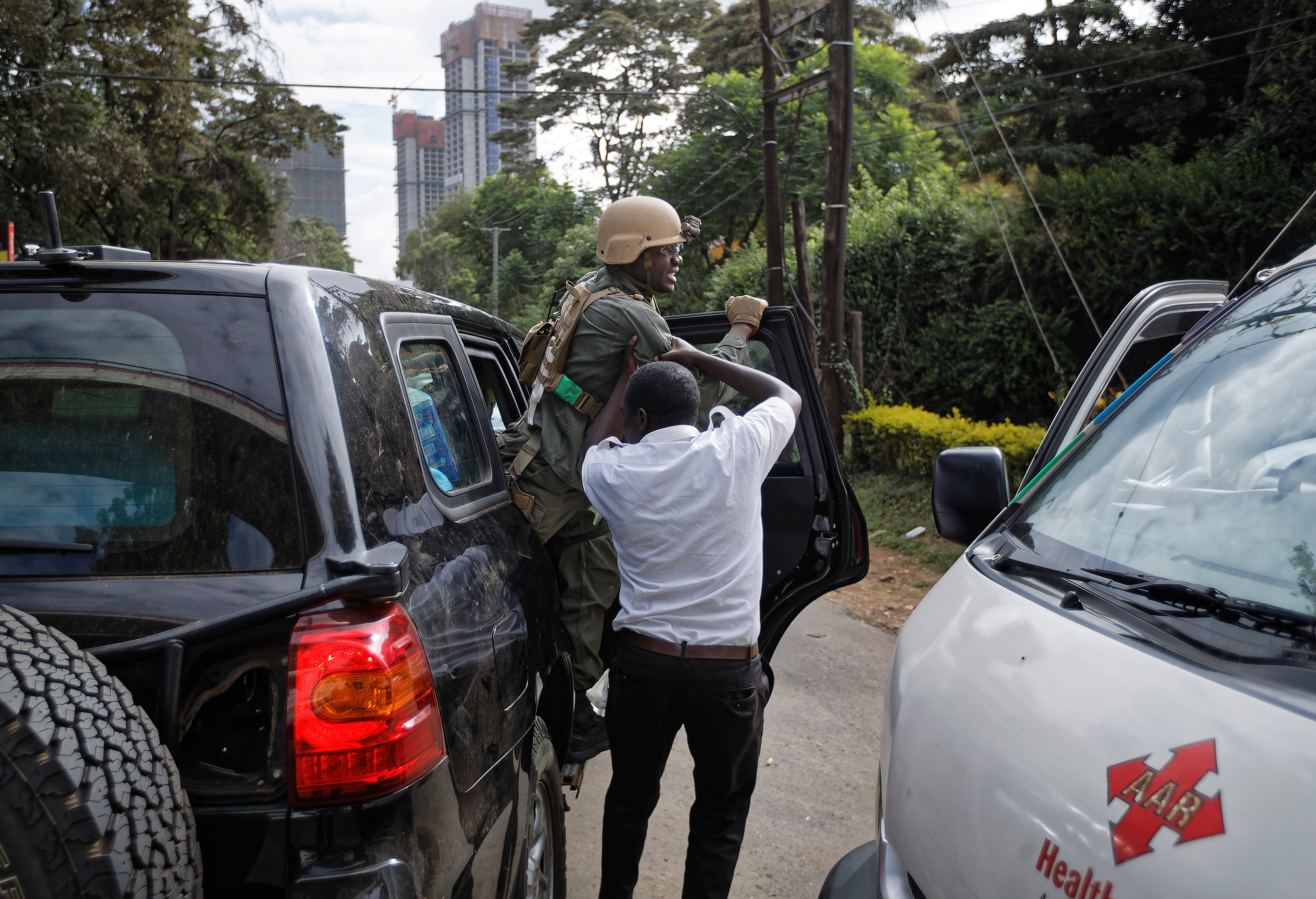A member of Kenyan special forces is helped out of a US embassy diplomatic vehicle by a paramedic at the scene Wednesday, Jan. 16, 2019 in Nairobi, Kenya. Extremists stormed a luxury hotel in Kenya's capital on Tuesday, setting off thunderous explosions and gunning down people at cafe tables in an attack claimed by Africa's deadliest Islamic militant group. (AP Photo/Ben Curtis) A wounded police officer is helped out of a US embassy diplomatic vehicle near the hotel attack, January 16, 2019 in Nairobi, Kenya. The officer is a member of a Special Program for Embassy Augmentation Response (SPEAR) team, whose members are trained and equipped by the Antiterrorism Assistance program to respond to crises involving the U.S. embassy. (AP/WideWorld Photos)