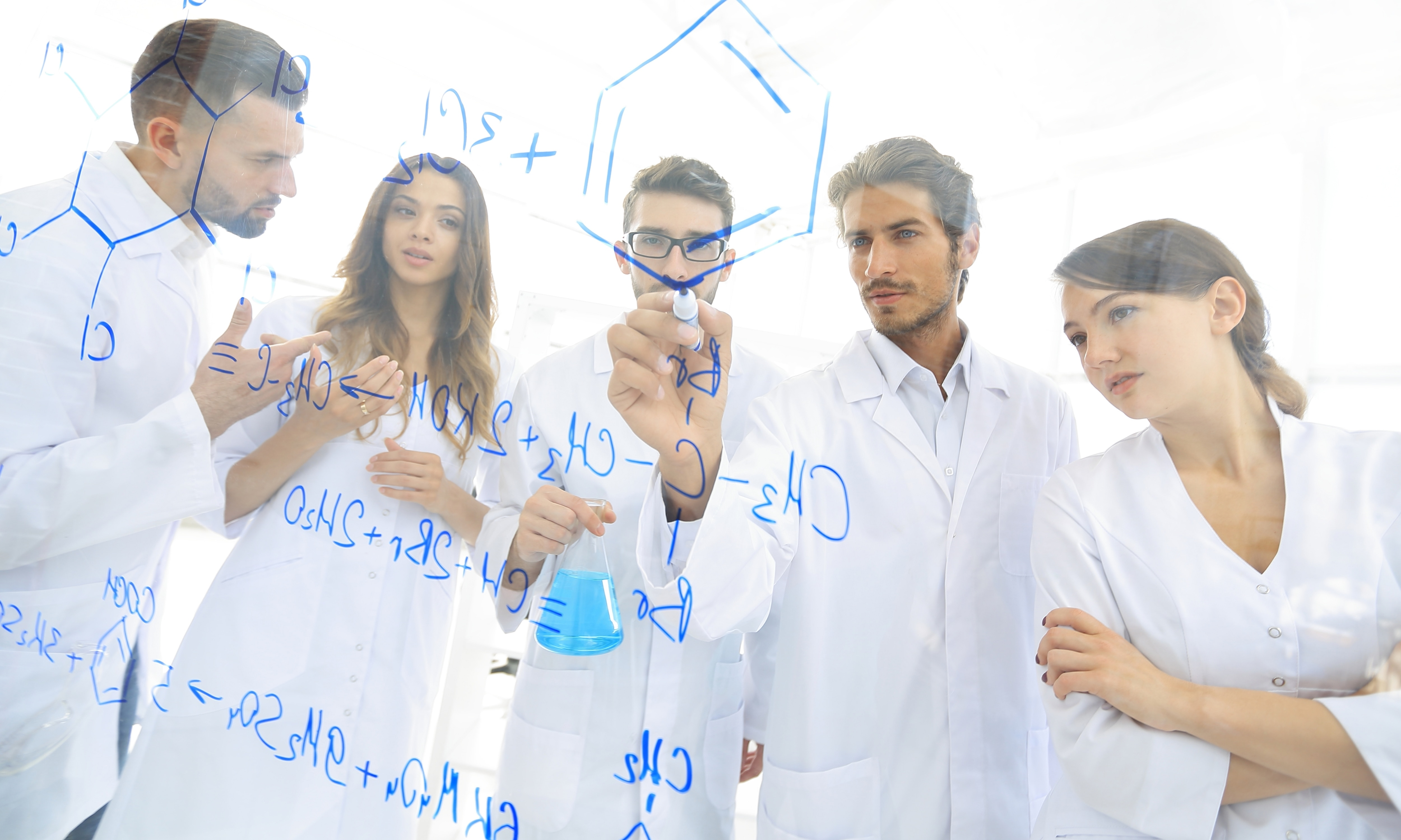 general-view seen trough a transparent board in a chemistry lab of people analyzing information - Image