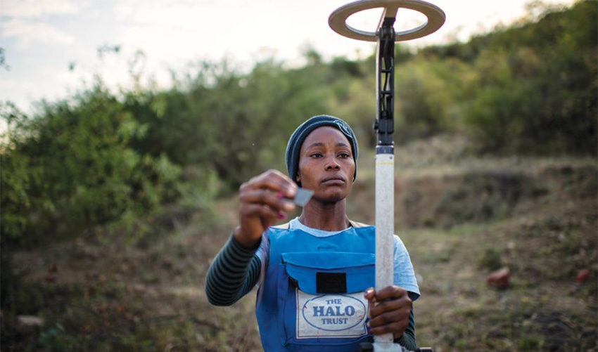 Date: 2019 Description: In Angola, a deminer tests her detector before beginning work. © Photo courtesy of HALO