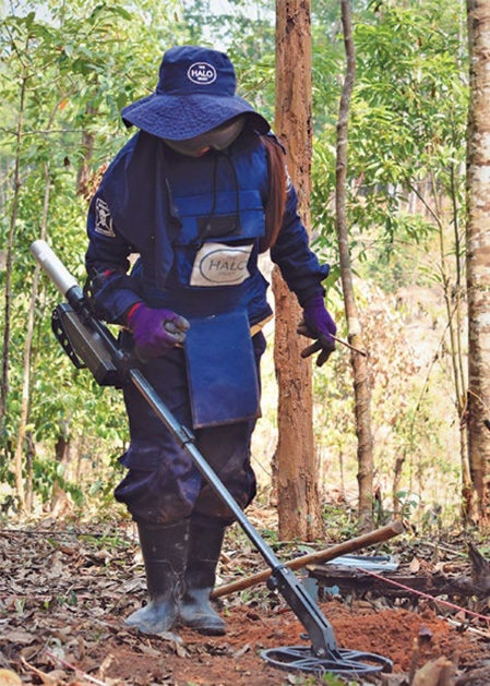 Date: 2019 Description: In Laos a deminer sweeps for signals looking for UXO. © Photo courtesy of HALO