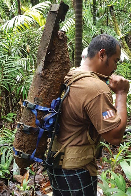 Date: 2019 Description: A World War II-era 100 lb bomb is carried out of the forest in Palau. © Photo courtesy of NPA