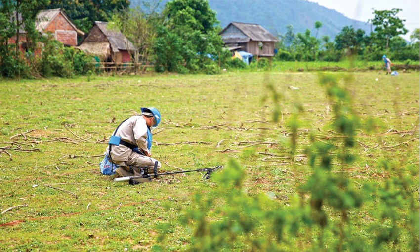 Date: 2019 Description: In Vietnam, a UXO clearance team works to clear a field adjacent to a village. © Photo courtesy of PeaceTrees