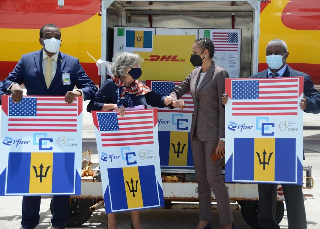 Two women bump elbows alongside two men holding up signs with U.S. and Barbados flag and Pfizer logo