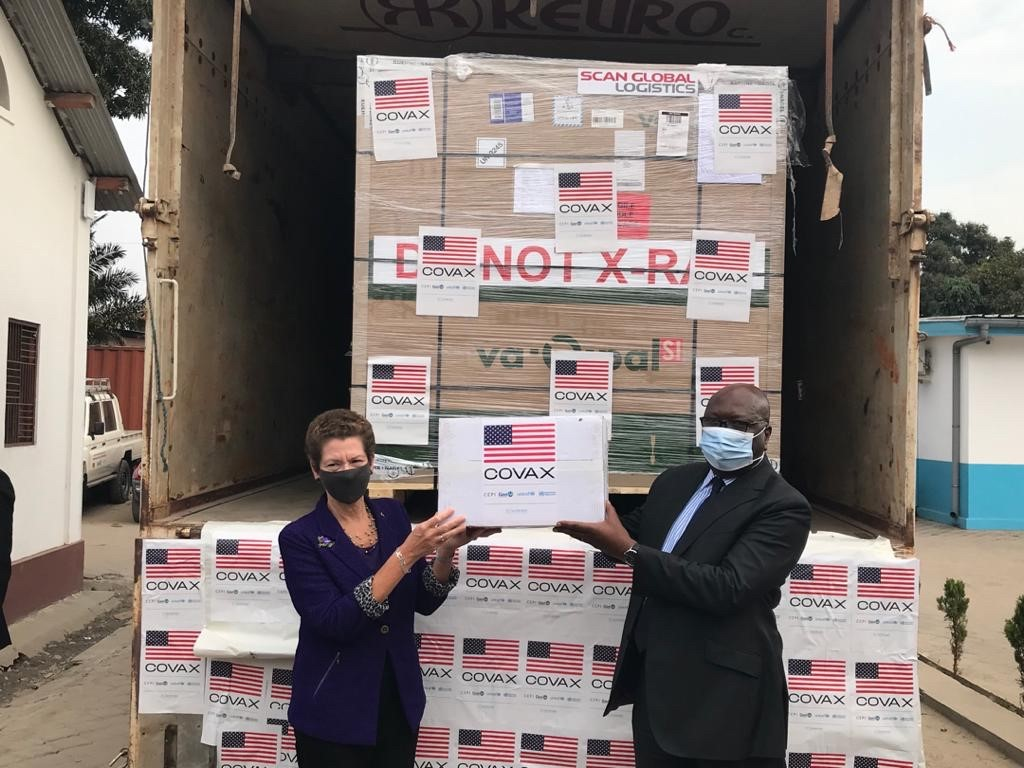 Two people in front of boxes, holding a sign reading COVAX and with an American flag