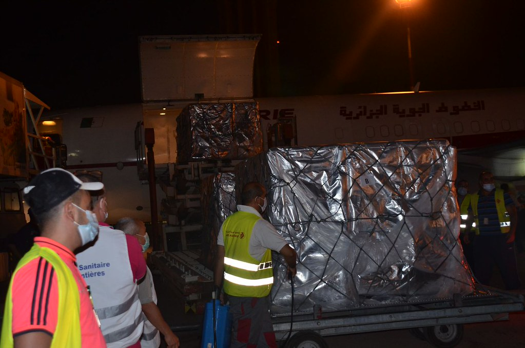 People unload boxes from a plane