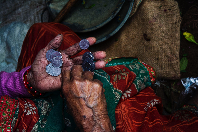 A woman's hands counting coins. (Riya Kumari; 2018)