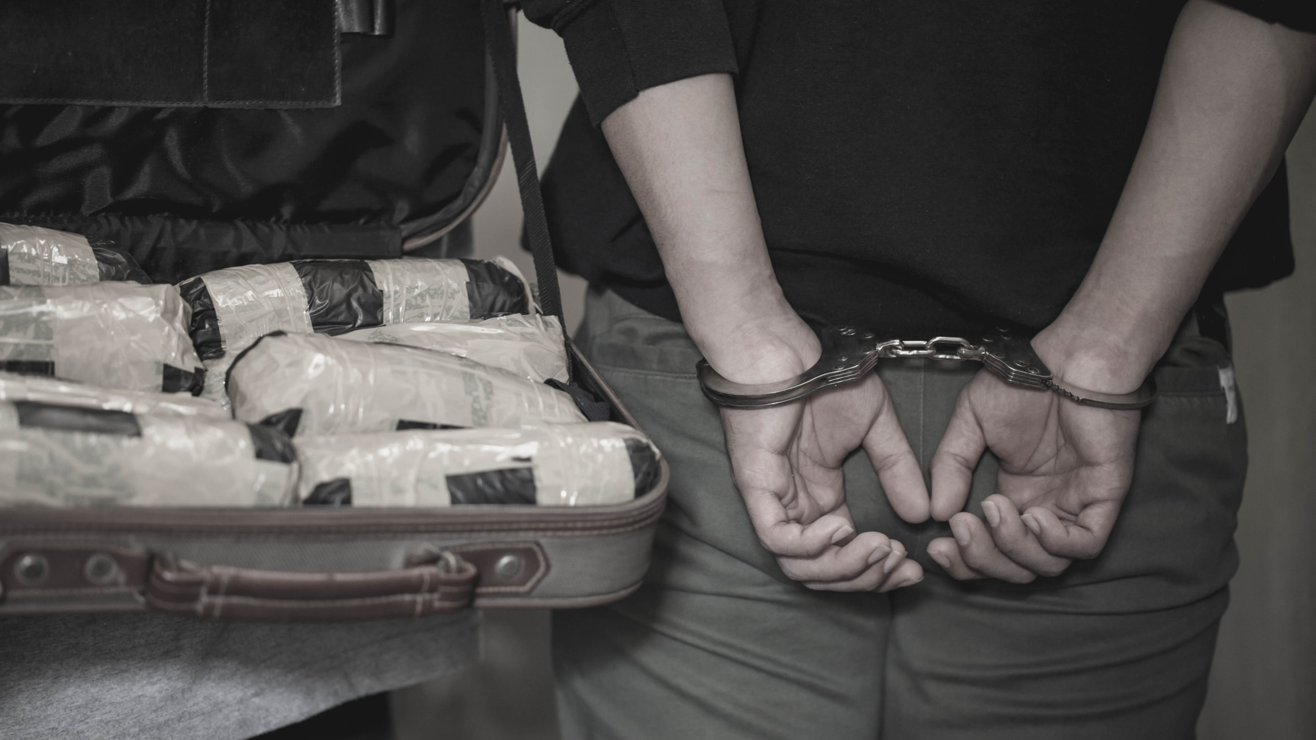 Police arrest drug trafficker with handcuffs. [Shutterstock]