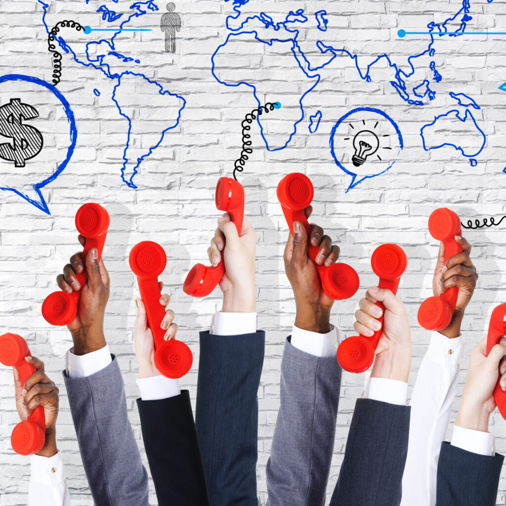 Business communication arms raised with telephone and world map. - Shutterstock Image