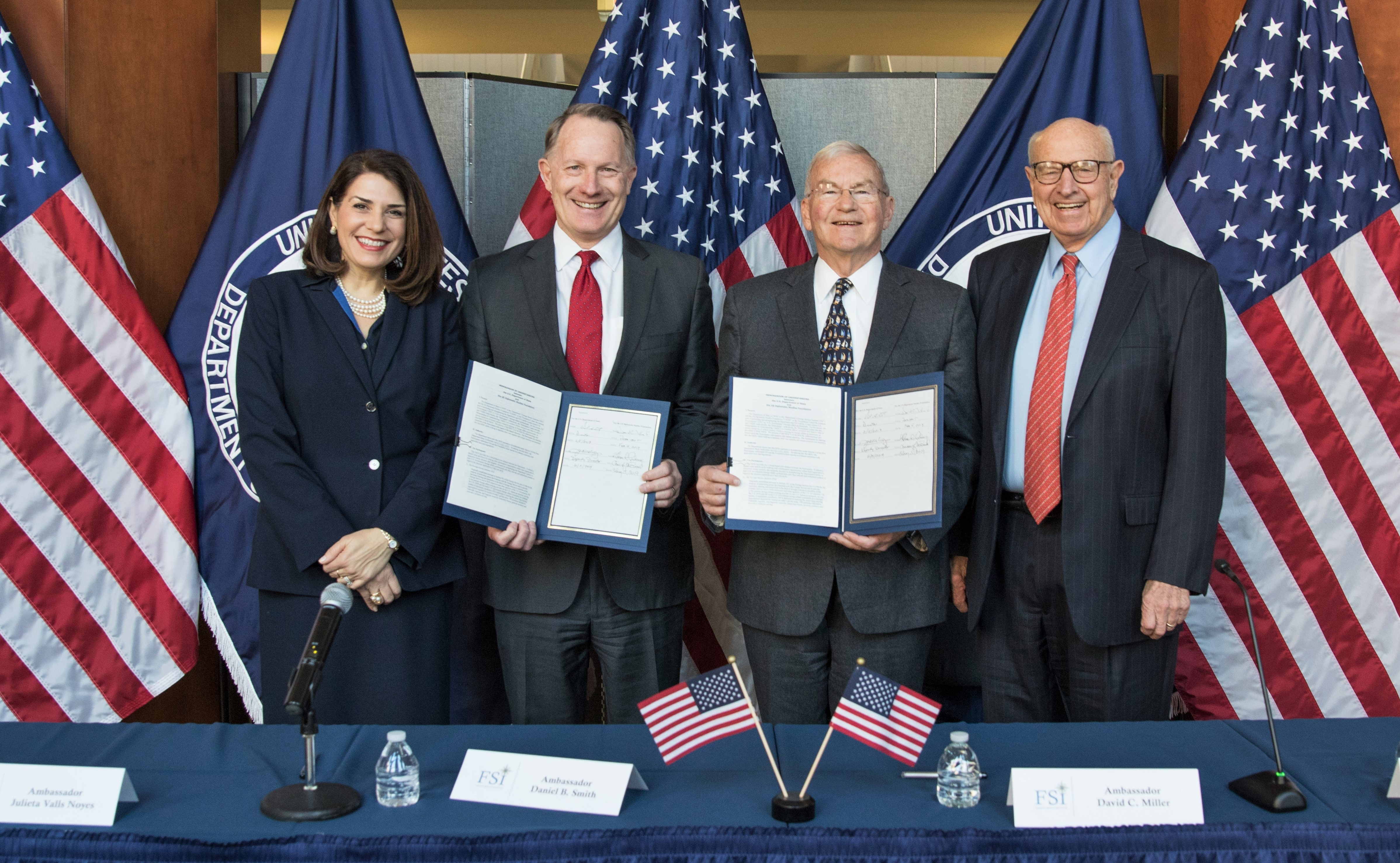 FSI Deputy Director Julieta Valls Noyes, FSI Director Daniel B. Smith, USDSF President David C. Miller, and USDSF Co-Chair Ambassador Thomas R. Pickering at the MOU signing ceremony. Ambassadors Smith and Miller hold the signed MOUs.