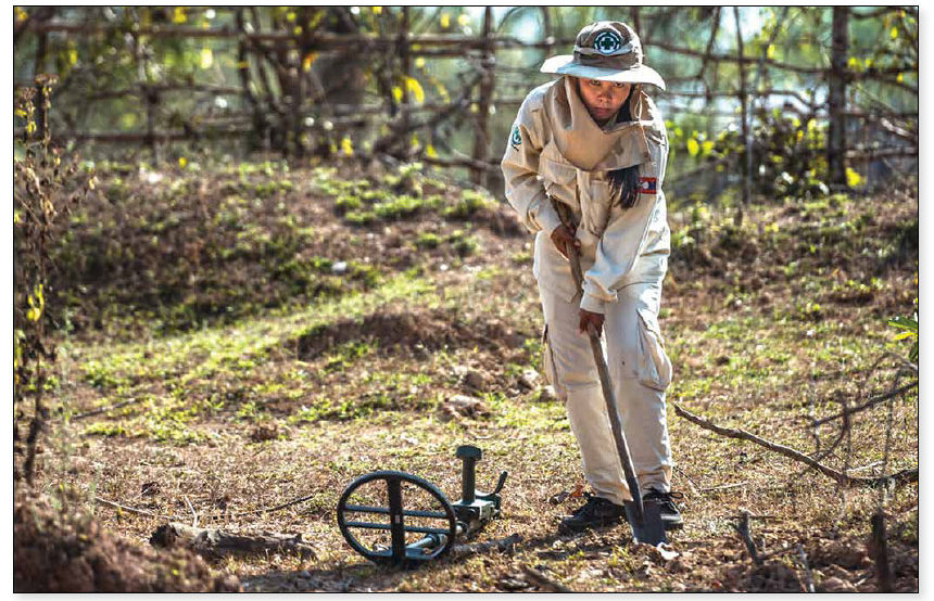 Date: 2018 Description: A Lao member of an NPA cluster munitions remnants survey team, funded by PM/WRA, carefully exposes an unexploded cluster munition. © Photo courtesy of NPA