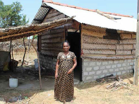 Date: 2018 Description: Sarasu in front of her temporary shelter and permanent bathroom, happy to be back home. © Photo courtesy of HALO