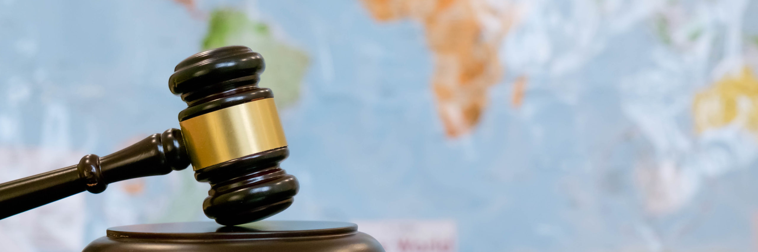 Judge's gavel and over world map. Symbol for jurisdiction. Law concept a wooden judges gavel on table in a courtroom or law enforcement office on blue background. Copy space for text - Image