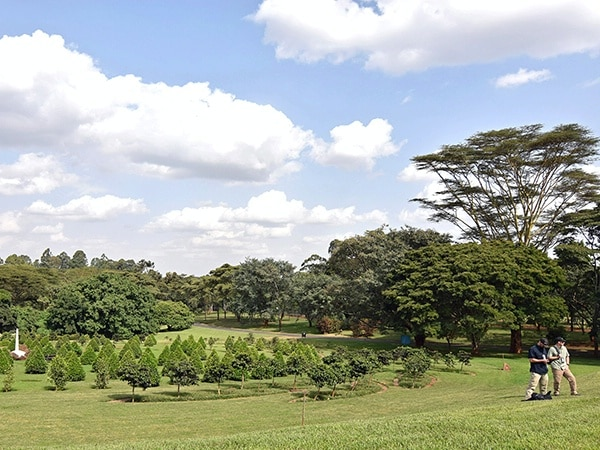 Diplomatic Security agents at the UN compound in Nairobi, Kenya, July 18, 2015, walk past a garden of remembrance planted after the 1998 U.S. embassy bombing by al-Qa'ida. The garden includes tea and coffee plants representing each individual killed in the attack. (U.S. Department of State photo)