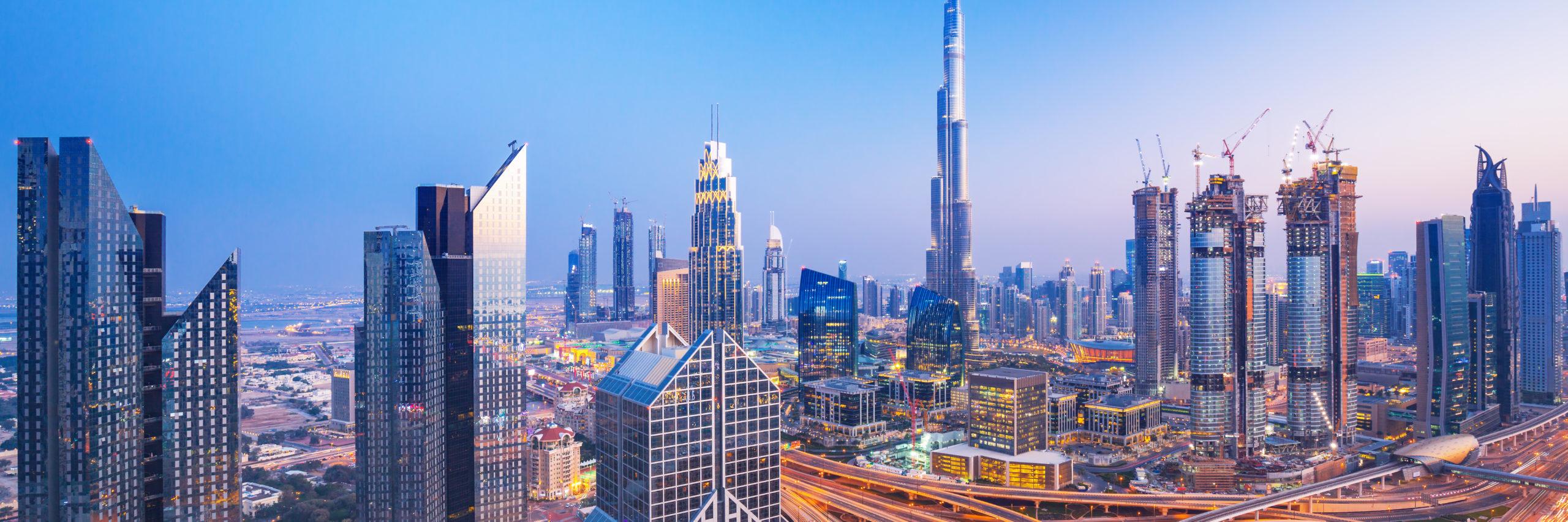 Dubai skyline at sunset with beautiful city center lights and Sheikh Zayed road traffic, Dubai, United Arab Emirates - Image