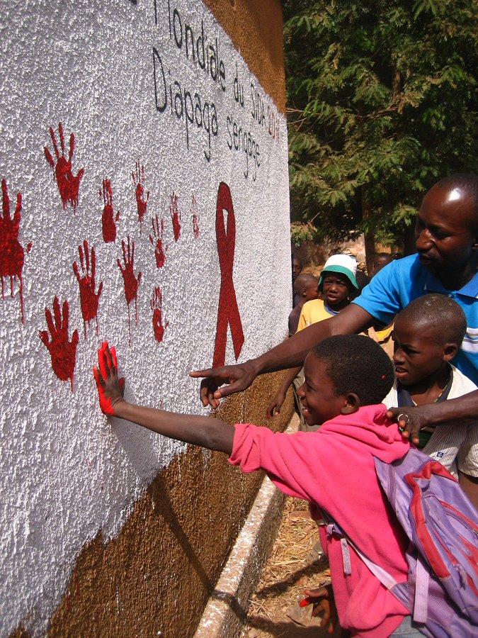 Children Making Hand Prints Beside An AIDS Ribbon