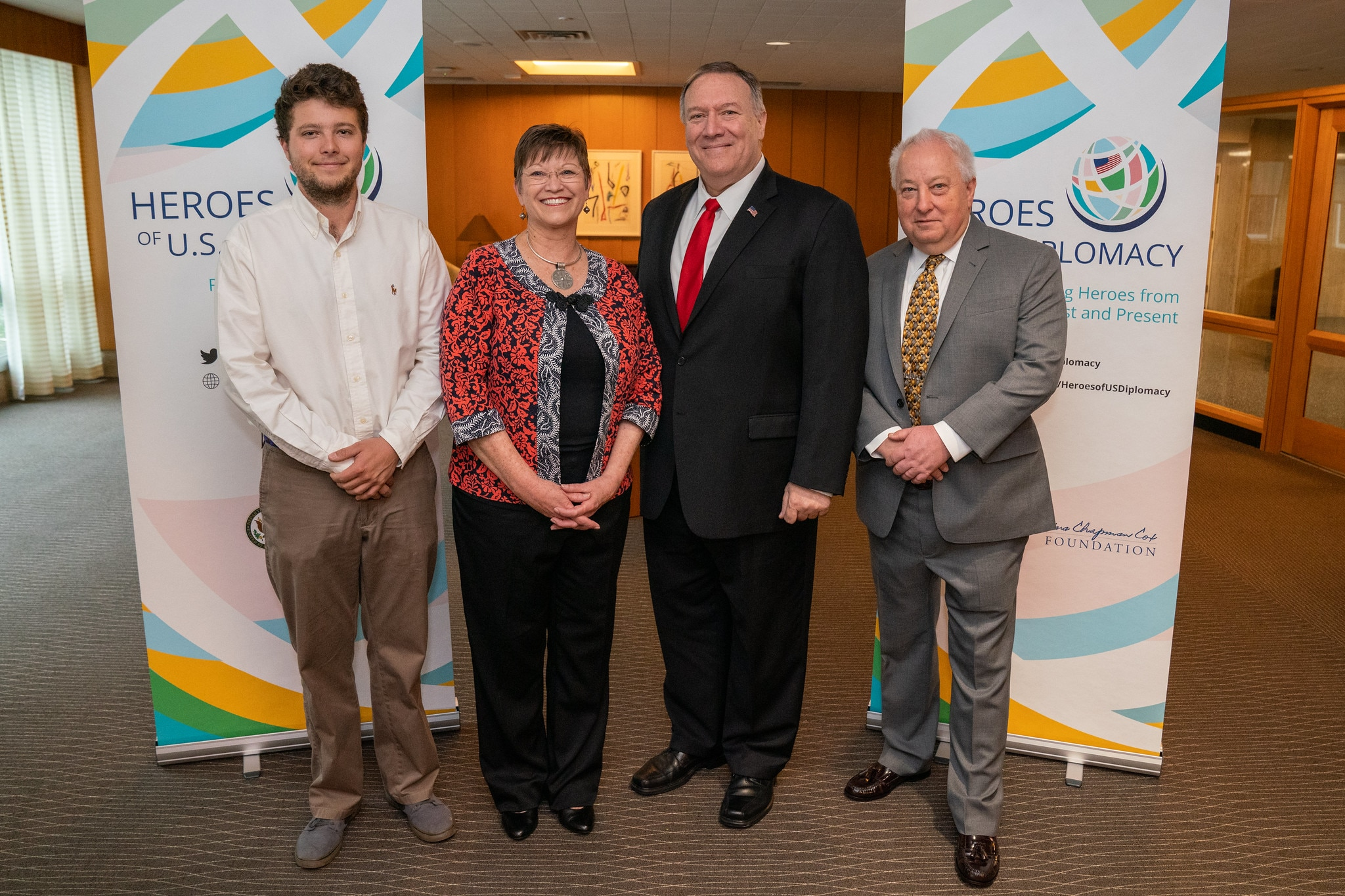 The inaugural Heroes of U.S. Diplomacy honoree, Elizabeth Slater, poses with U.S. Secretary of State Michael R. Pompeo and her family members in front of Heroes of U.S. Diplomacy banners.