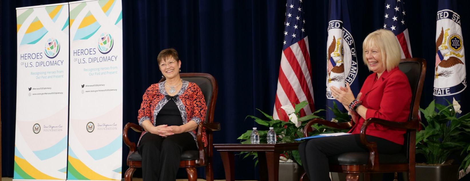 Elizabeth Slater and Director General Carol Perez sit in armchairs on the stage for the launch of the Heroes of U.S. Diplomacy initiative.