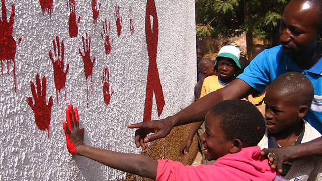People putting their handprints on a wall with a red ribbon