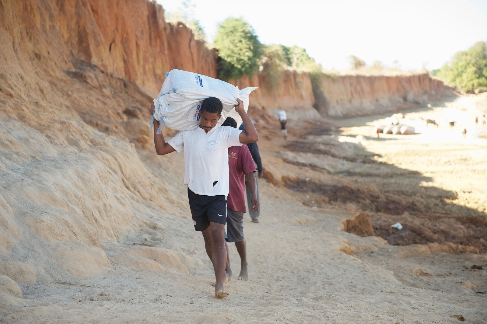 Malaria nets are carried by back during the final leg of the delivery journey. (Lan Andrian, USAID Global Health Supply Chain Program—Procurement and Supply Management)