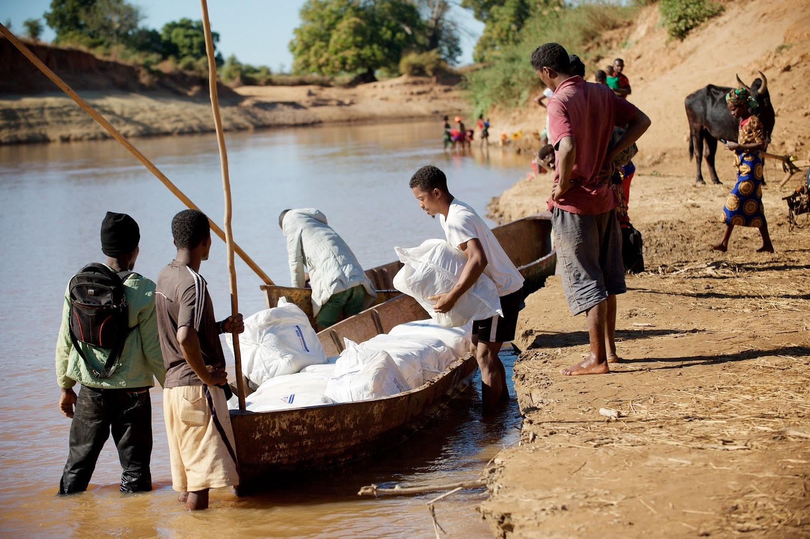 Malaria nets are placed onto pirogues to be transported across a river. (Lan Andrian, USAID Global Health Supply Chain Program—Procurement and Supply Management)