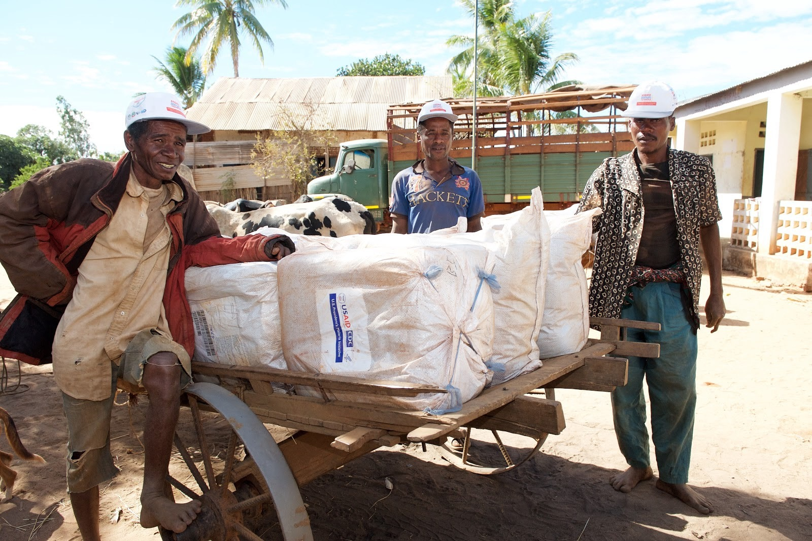 Malagasy men load malaria bed nets onto a cart in preparation for distribution. (Lan Andrian, USAID Global Health Supply Chain Program—Procurement and Supply Management)