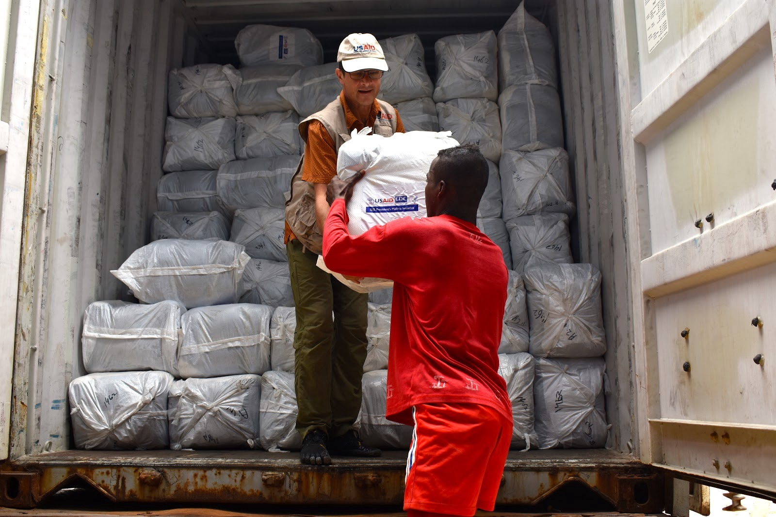 Bed nets are off-loaded from trucks into a warehouse in Antananarivo. (Anne Daugherty, USAID Madagascar)