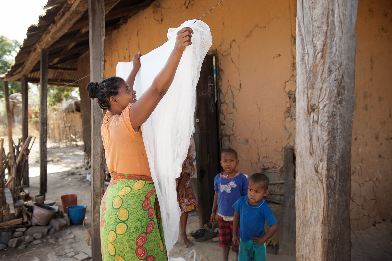 Florentine, a beneficiary from Boriziny, unfolds her newly delivered insecticide-treated bed net. (Lan Andrian, USAID Global Health Supply Chain Program—Procurement and Supply Management)
