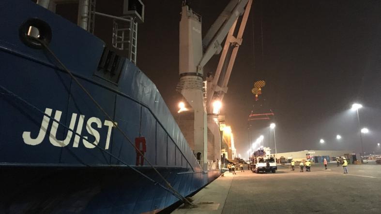 Crews start loading the cranes onto the cargo ship MV Juist. (USAID/OFDA)