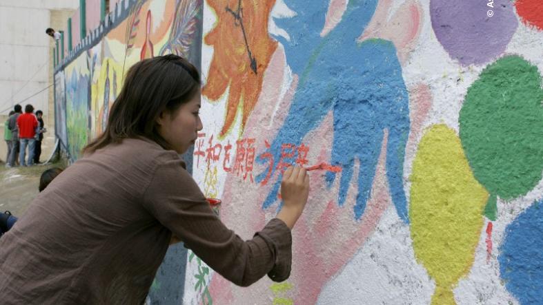 A woman paints a pro peace mural painting.