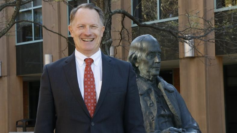 Ambassador Daniel B. Smith poses for a photo on the campus of the Foreign Service Institute alongside a statue of our nation's first diplomat – Ben Franklin.