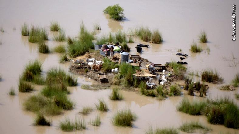 Pakistani flood affected people look towards an army helicopter which was dropping relief supplies at the heavily flooded area of Rajanpur, in central Pakistan.