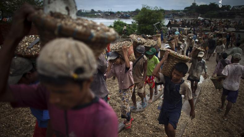 A child carries a basket of stones while unloading a quarry boat with adult workers at a port in Myanmar. (AP Photo)