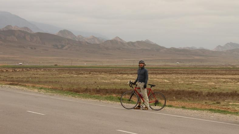 Information Officer J.R. deLara in front of the Kopetdag Mountains, during a cross-Turkmenistan public outreach bike trip. (Photo courtesy of Alex Koch)
