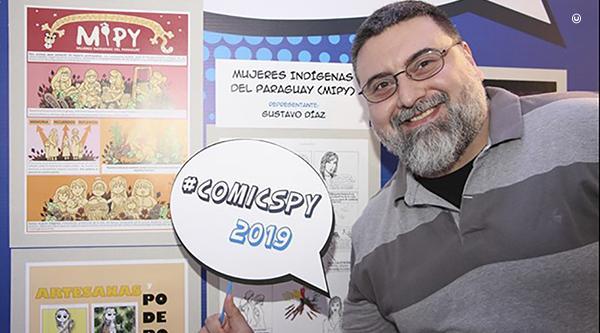 Paraguayan illustrator Gustavo Diaz poses next to the #ComicsPy exhibit of Mujeres Indigenas del Paraguay (Indigenous Women of Paraguay) during the 2019 National Book Festival in Asuncion.