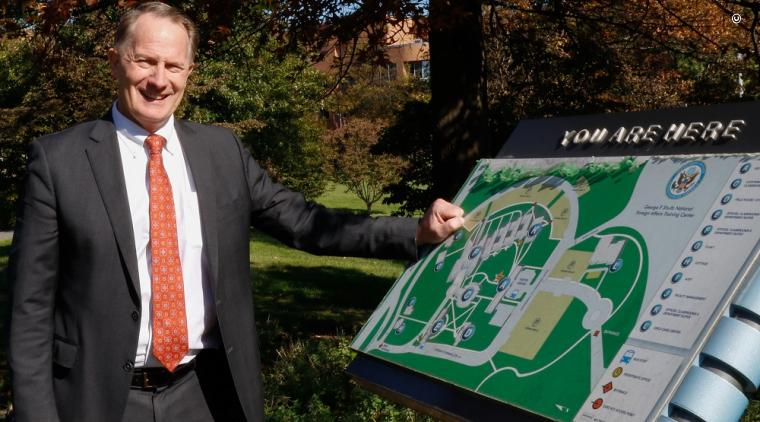 Ambassador Daniel B. Smith poses for a photo near a campus map at the Foreign Service Institute in Arlington, Virginia.