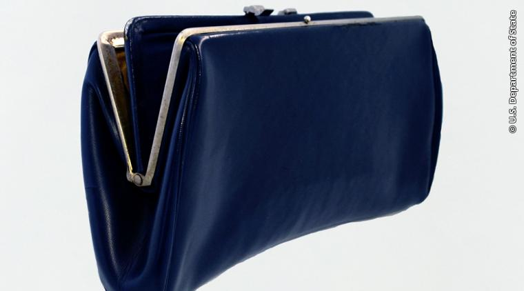 """This clutch purse belonged to Patricia Morton, also known as """"Pistol Packing Patti,"""" the first woman to become a Diplomatic Security Special Agent. In the absence of gear made specifically for women, Morton used this dark blue clutch to carry her DS-issued .357 Magnum Revolver.  Gift of Patricia """"Patti"""" Morton"""