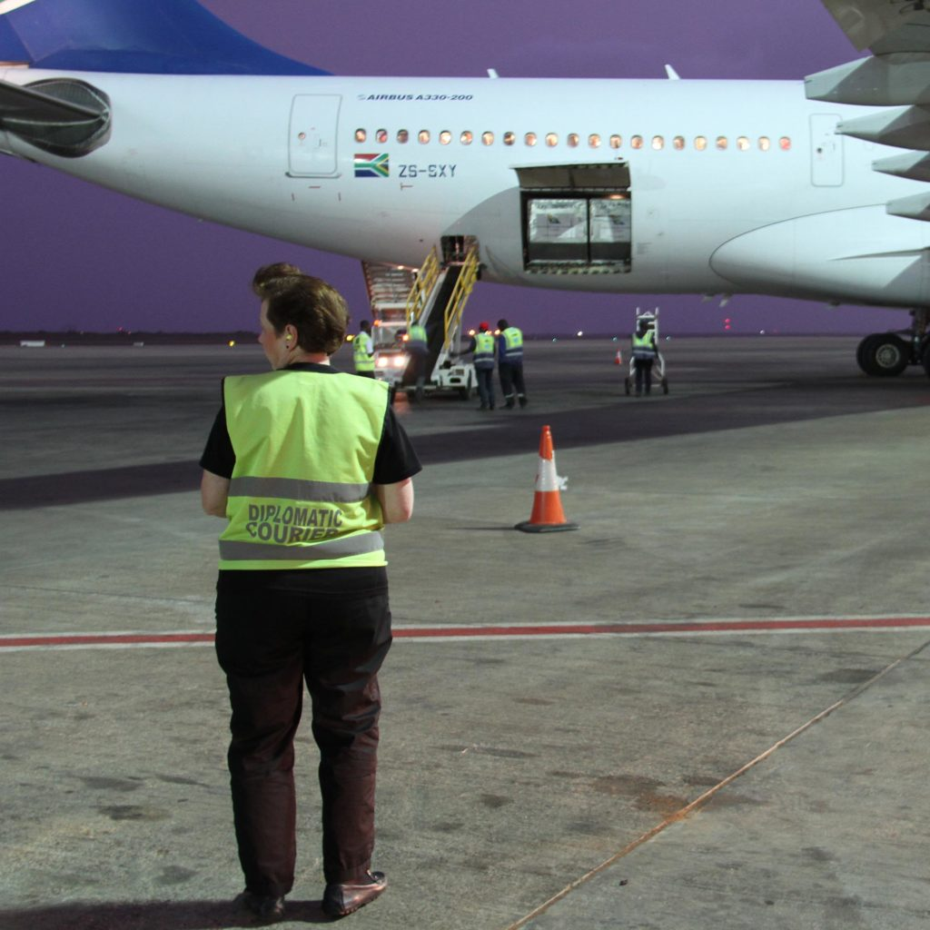 A female courier wearing a yellow reflective vest with the words Diplomatic Courier stands in the foreground. A white aircraft with its cargo hold open is in the background.