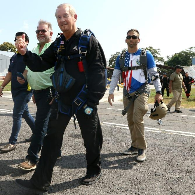 DSS Special Agent Zach Bowen (in a Red/White/Blue T-shirt) escorts U.S. Ambassador to El Salvador Ronald Johnson (in a black jumpsuit) to the plane for a bit of skydiving in the Ilopango Airshow, Ilopango, El Salvador, Feb. 1, 2020. (U.S. Department of State photo)