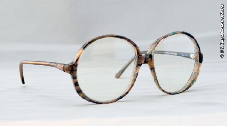 """These eyeglasses were worn by U.S. Embassy Tehran Consular Assistant Kathleen Stafford as part of her disguise during a covert CIA operation to exfiltrate her and five other embassy employees from Iran on January 28, 1980. Known as the """"Canadian Six,"""" they were sheltered in the homes of Canadian Embassy officials in Tehran after they avoided capture by student militants who seized the U.S. Embassy on November 4, 1979. The CIA operation was dramatized in the popular 2012 film """"Argo.""""  Gift of Kathleen Stafford"""