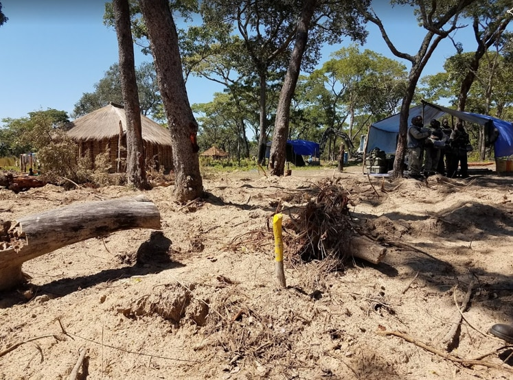 The yellow stake indicates where MAG found and destroyed an anti-personnel landmine in Moxico province under a U.S.-funded project. Note the proximity of the landmine to the house in the background. (Department of State photo)