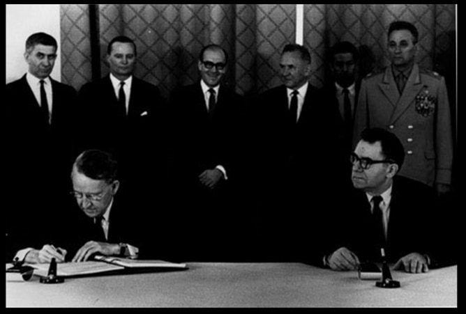 U.S. Ambassador Llewellyn E. Thompson, left, signs nuclear non-proliferation treaty as Soviet Foreign Minister Andrei A. Gromyko watches in Moscow, Russia, on July 1, 1968. Standing, left to right are, Embassy Political Counsellor David Klien, U.S. Embassy Scientific Attache Christopher Squire, U.S. (Caption by U.S. Embassy Norway)