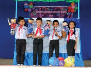 Children in Laos perform a puppet show they learned during an MRE class. Photo courtesy of World Education.
