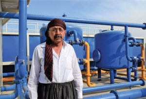 Faisal in front of the repaired water purification plant in Tulaband. Photo courtesy of MAG.