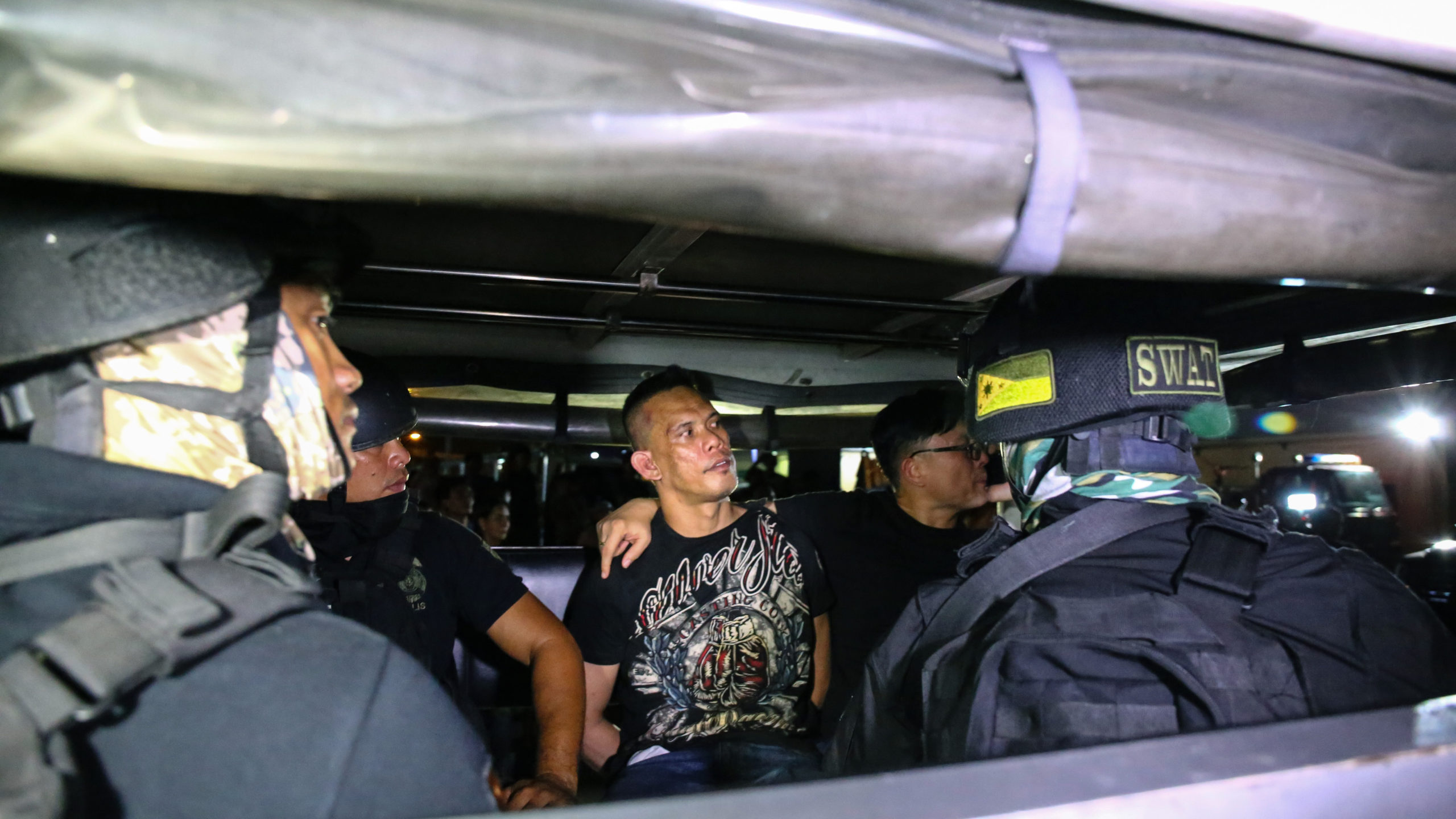 The hostage taker (center) sits inside a police vehicle after his arrest at the V-Mall in Manila, March 2, 2020. (AP/Wide World Photos)