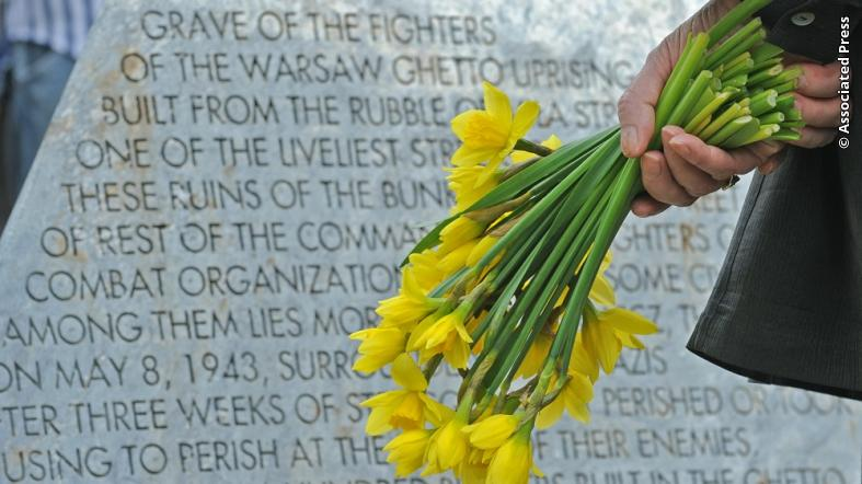 A woman stands with flowers in front of a memorial stone during a ceremony marking the anniversary of the beginning of the Warsaw Ghetto Uprising, in Warsaw, Poland. (Associated Press photo)
